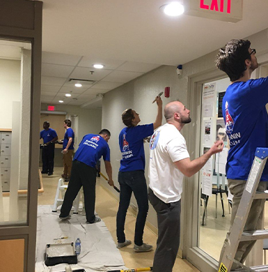 Group of volunteers are painting a hall way